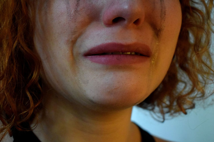 Cropped image of woman with smudged make-up crying