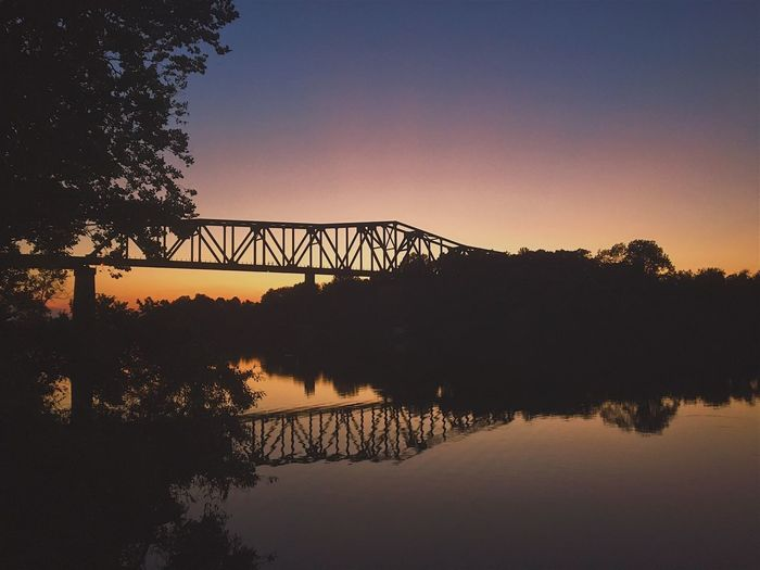 Silhouette of bridge over river at sunset