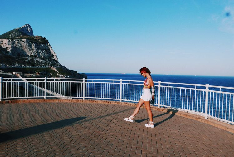 Side view of young woman walking at promenade