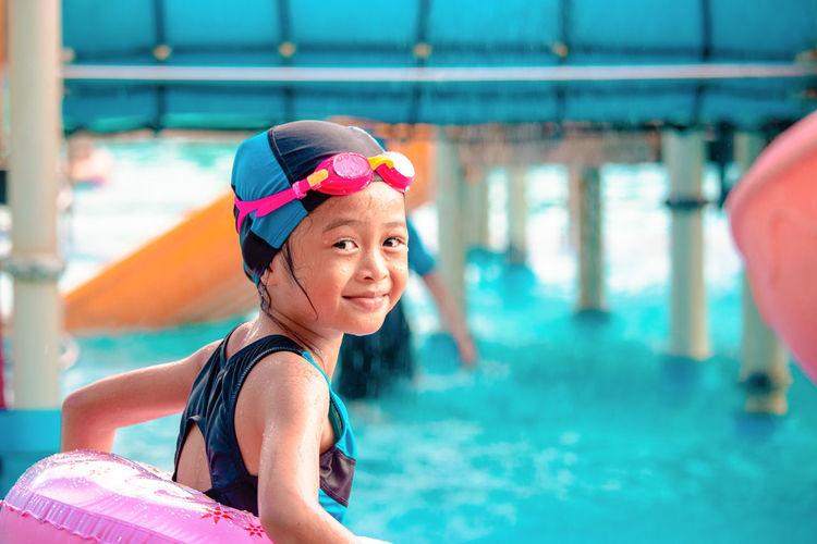 Cute girl standing in swimming pool