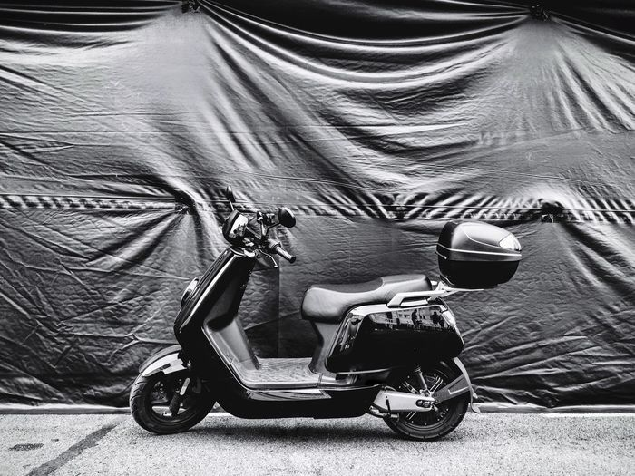 Motor scooter against fabric