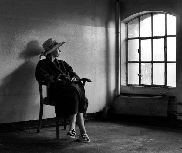 Full length of woman sitting on chair in abandoned house