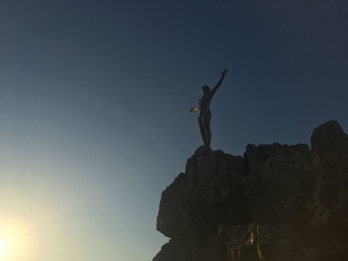 Ready to take the leap Sky Low Angle View Nature One Person Human Arm Leisure Activity Rock Silhouette Rock - Object Lifestyles Men Clear Sky Standing Human Representation Real People Solid Freedom Copy Space Arms Raised Outdoors