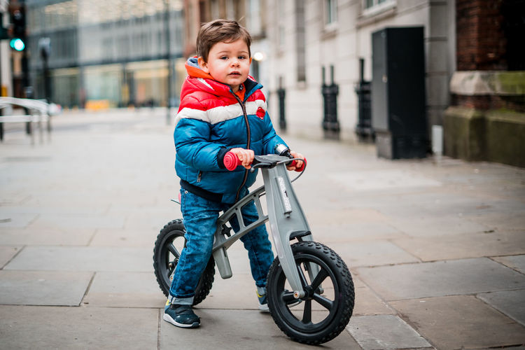 Boy with bicycle in city