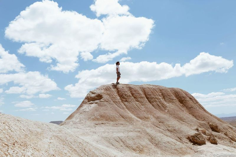 Man Standing On Rock Formation Against Sky