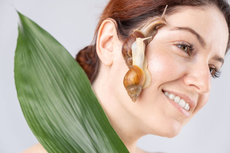 Close-up of smiling young woman with snail of face