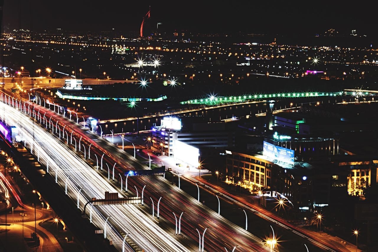 HIGH ANGLE VIEW OF ILLUMINATED BRIDGE AND BUILDINGS IN CITY