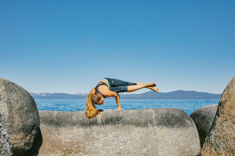 Woman on rocks by sea against clear blue sky