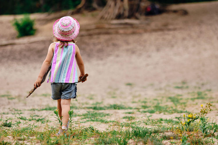 Rear view of girl walking on land