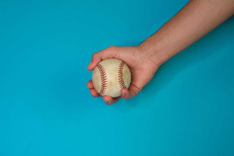 Close-up of hand holding a ball against blue background