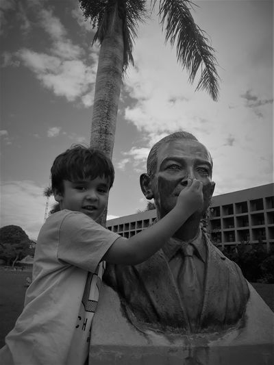 Portrait of boy holding statue nose in city