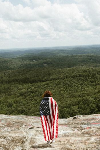 Rear View Of Woman Holding American Flag While Standing On Mountain
