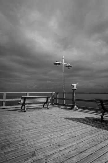 Empty Benches And Telescope On Floorboard By Baltic Sea Against Cloudy Sky