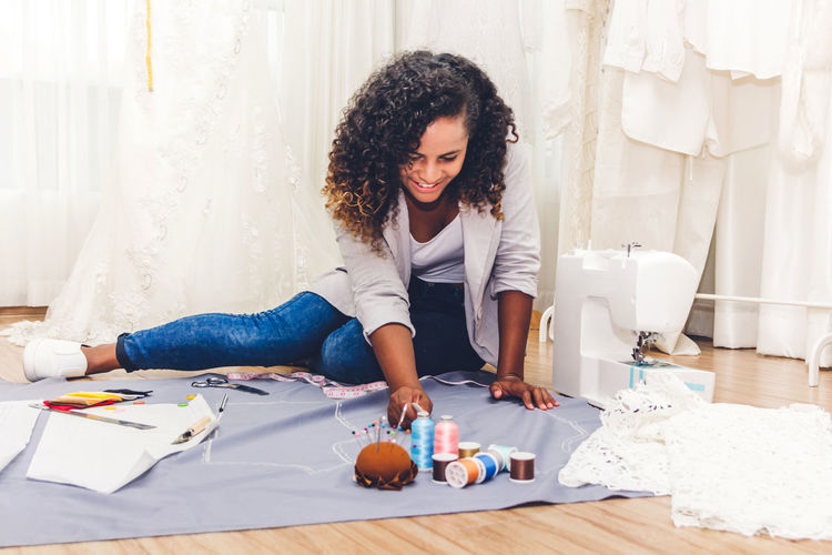 Young fashion designer measuring fabric at home office