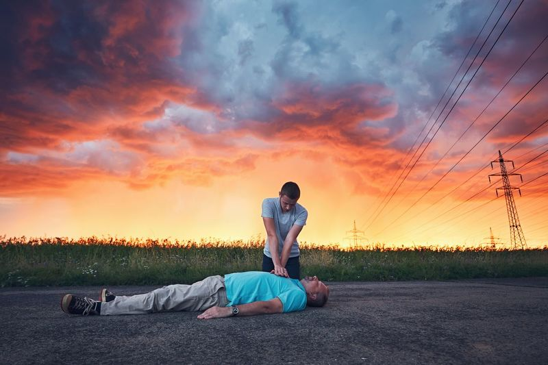 Man resuscitating friend lying on road against cloudy sky during sunset