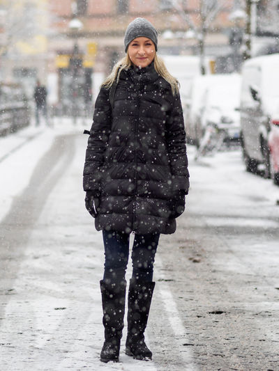 Portrait of smiling woman standing on snow