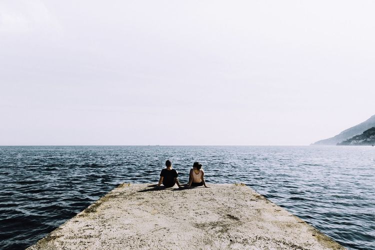 People sitting by sea against clear sky