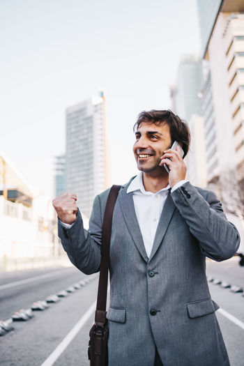 Smiling businessman talking over mobile phone while standing on road