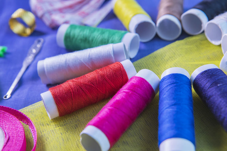 High angle view of colorful sewing items on fabric