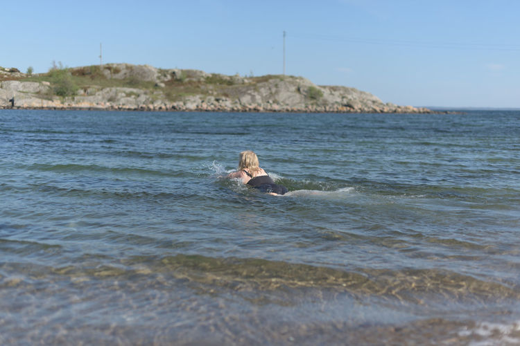 Scenic view of swimming in sea against sky