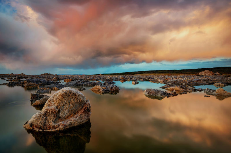 Panoramic view of rocks on shore against sky during sunset
