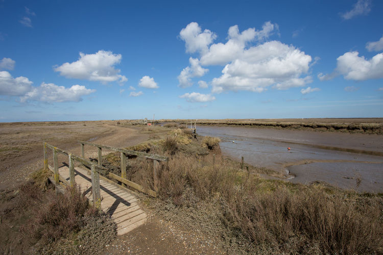 View across Morston Creek, Morston, Norfolk, England Copy Space Footbridge Morston Creek Norfolk Uk Beauty In Nature Blue Cloud - Sky Day Environment Grass Horizon Horizon Over Land Land Landscape Nature No People Non-urban Scene Outdoors Plant Remote Scenics - Nature Sky Tranquil Scene Tranquility Wooden