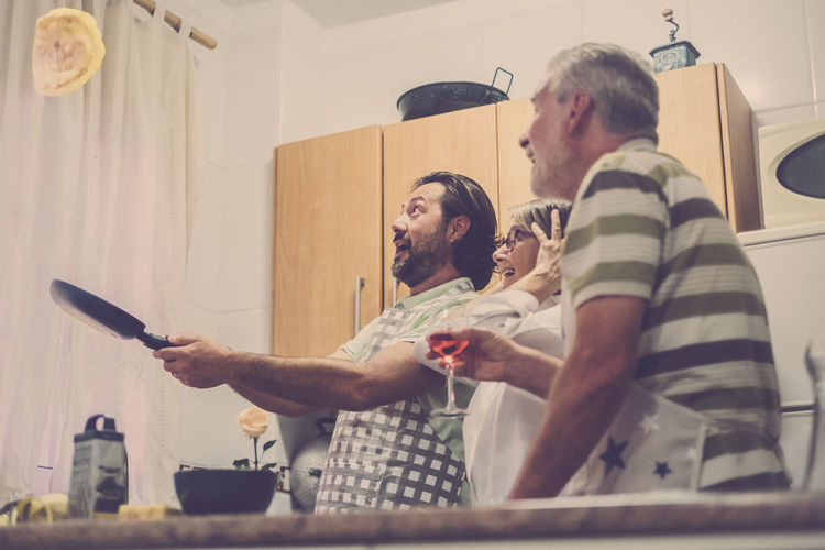 Mature son throwing omelette in pan while happy parents looking in kitchen