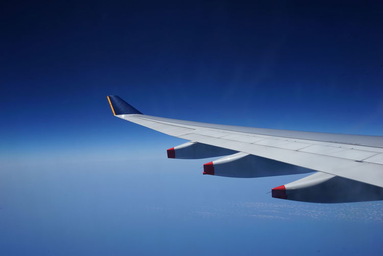 Cropped airplane wing against clear blue sky