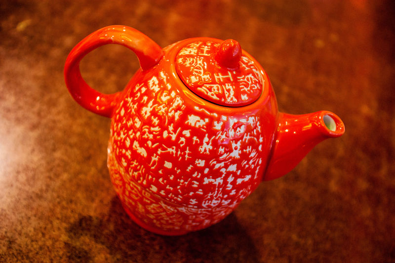 Close-up of orange kettle on table