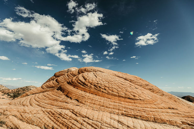 Low angle view of rocks on field against sky
