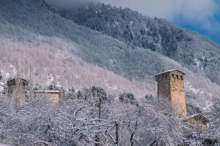 Cold Temperature Winter Mountain Built Structure Architecture Snow Building Exterior Nature Tree Sky Plant No People Scenics - Nature Frozen Building Beauty In Nature Day History Environment Outdoors Snowcapped Mountain Climate Mestia Old Village Castle