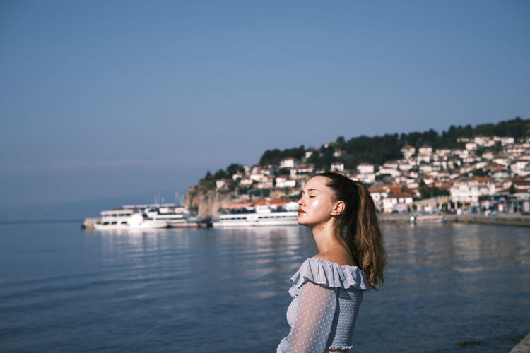 Smiling young woman standing by lake against sky in ohrid city