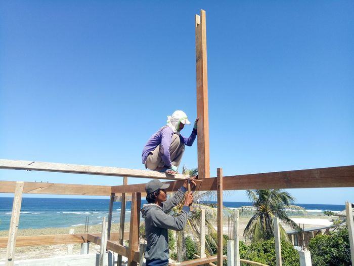 People working on railing against clear blue sky