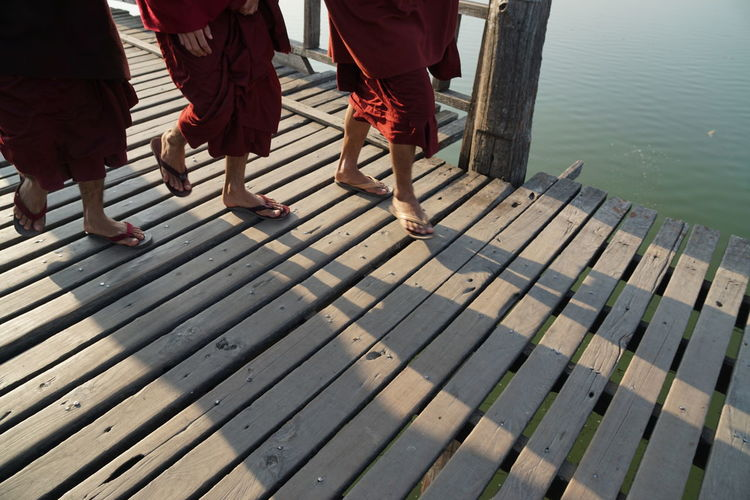 Low Section Of Monks Walking On Wooden Bridge