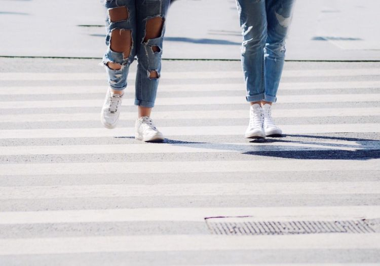 Low Section Of Women Walking On Zebra Crossing During Sunny Day