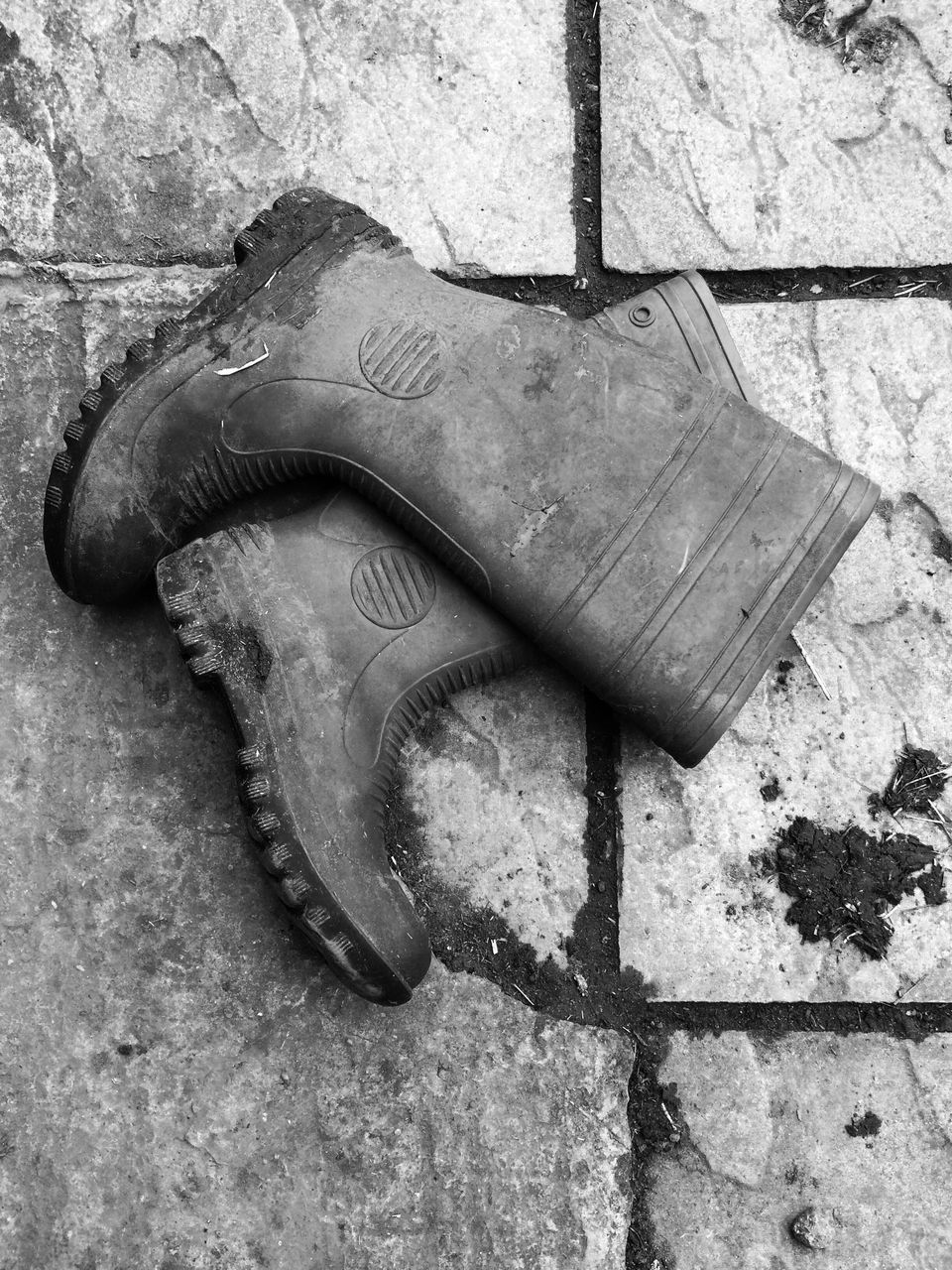 High Angle View Of Rubber Boots On Footpath