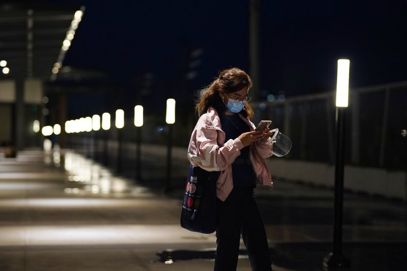 Young woman wearing mask using mobile outdoors