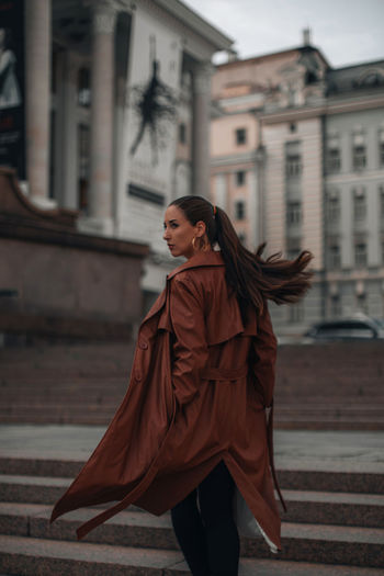 Outdoor autumn portrait of young elegant fashionable woman wearing trendy brown leather coat