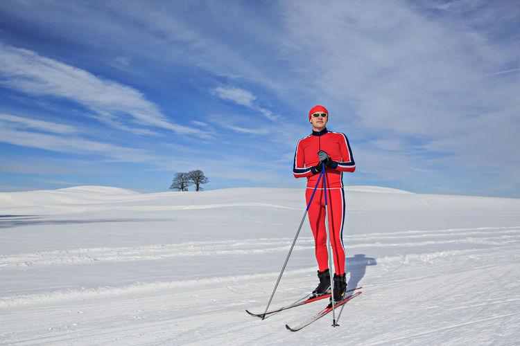 Full length of man skiing on snowy field against sky