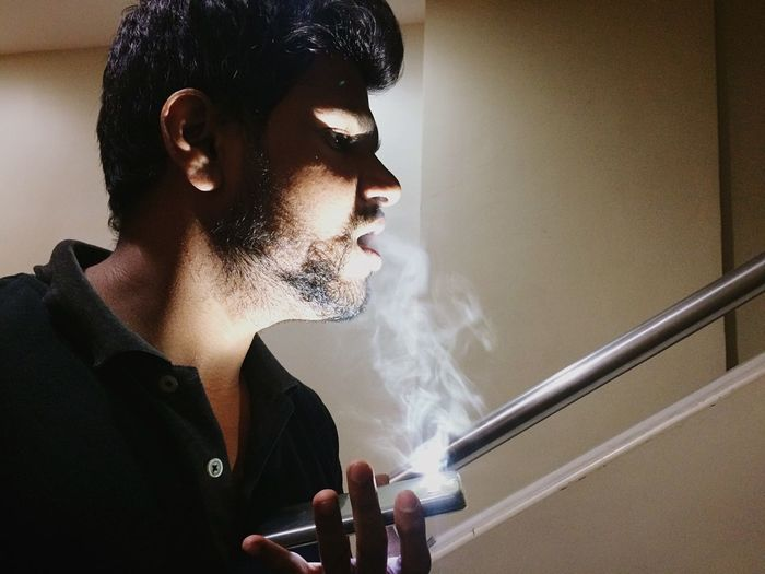 Close-Up Of Man Smoking Against Wall