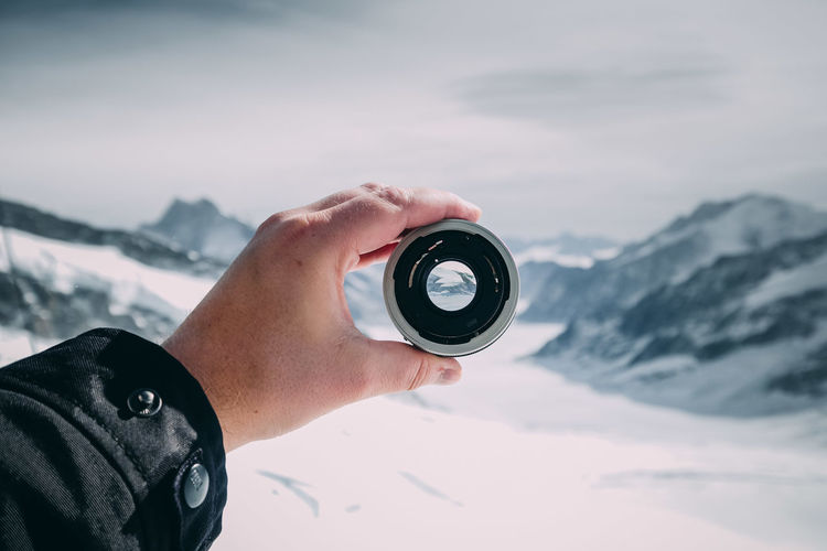 Cropped image of hand holding lens against snowcapped mountains