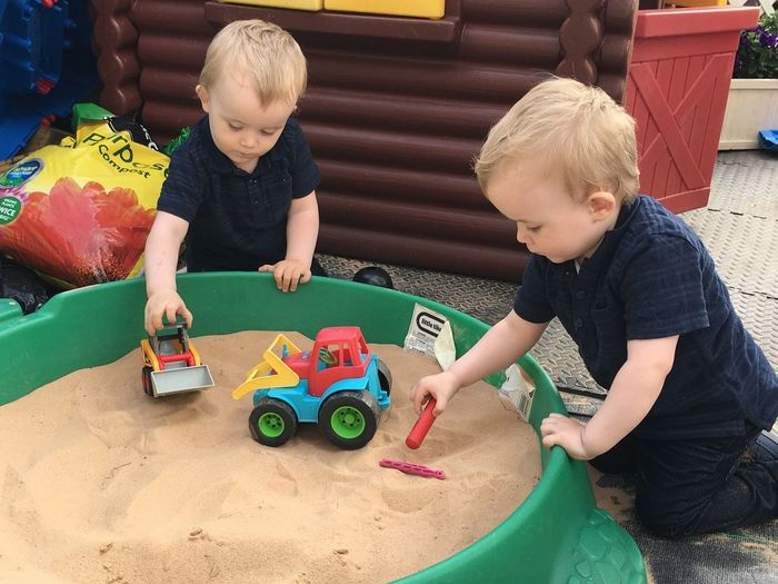 Cute twins brothers playing with toys on sandbox in preschool