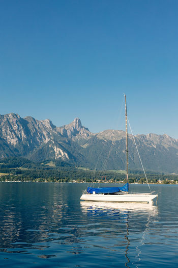 Sailboats in lake against clear blue sky