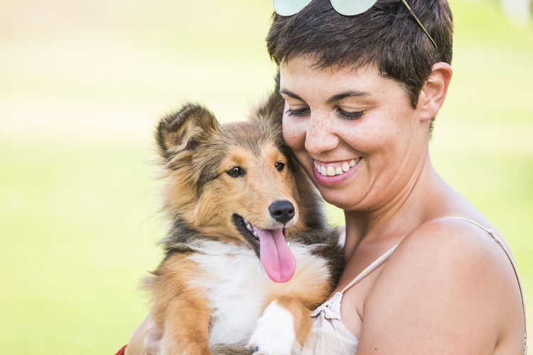 Smiling woman carrying dog in park