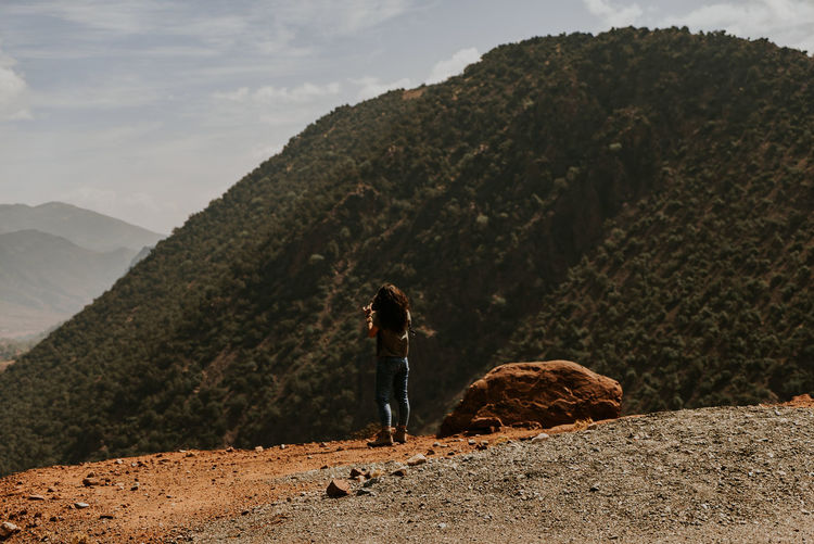Rear view of woman standing on rock against mountain