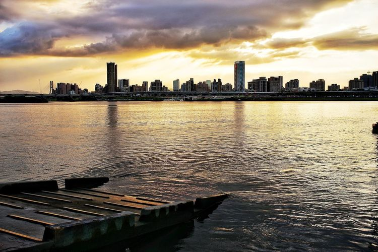 River amidst buildings in city against sky at sunset
