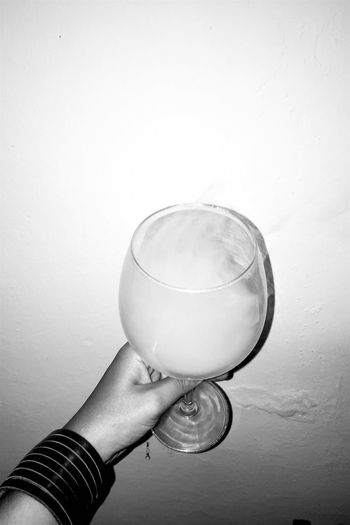 Close-up of hand holding wineglass against white background