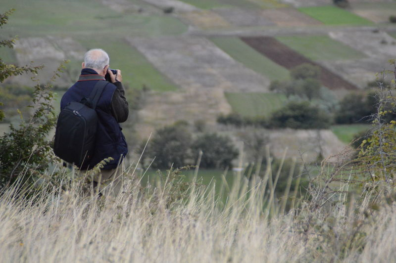Rear view of man photographing in field