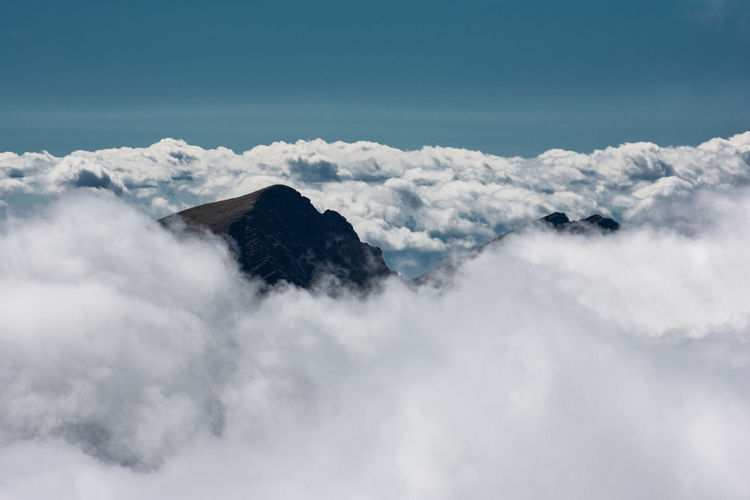 Scenic view of clouds covering mountains against sky