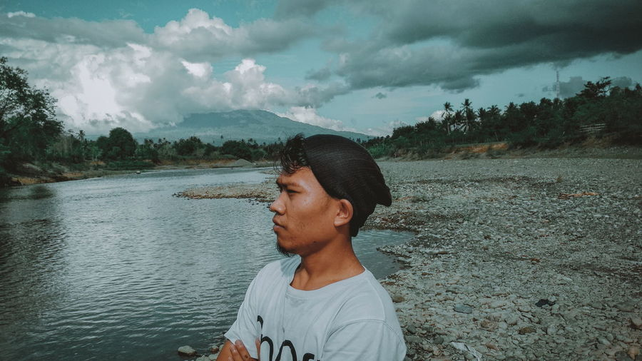 Side view of young man standing by river against cloudy sky